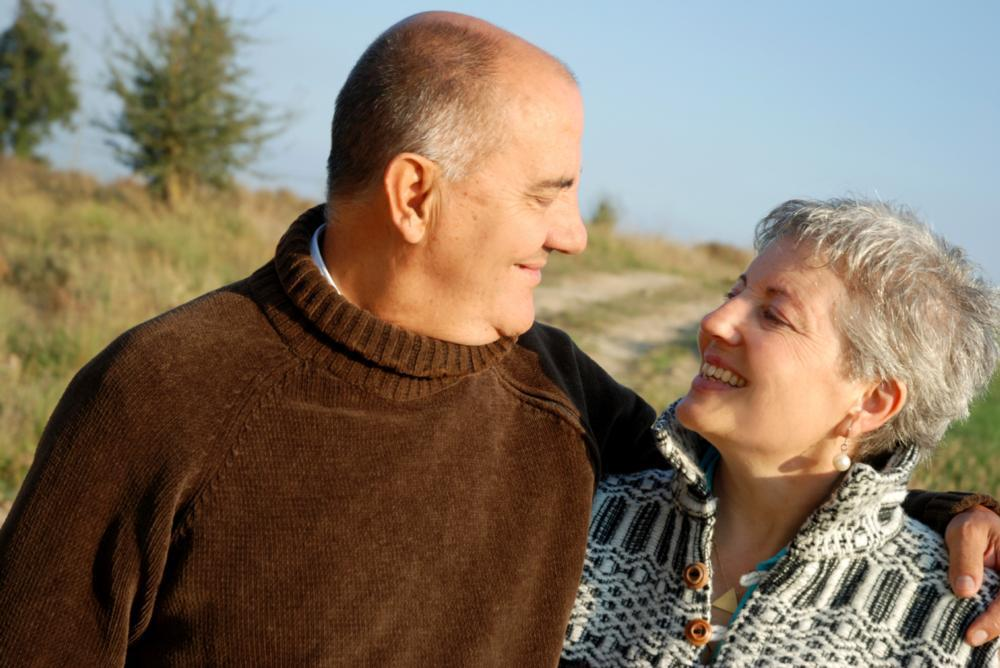 Older man smiling at older woman while on a walk