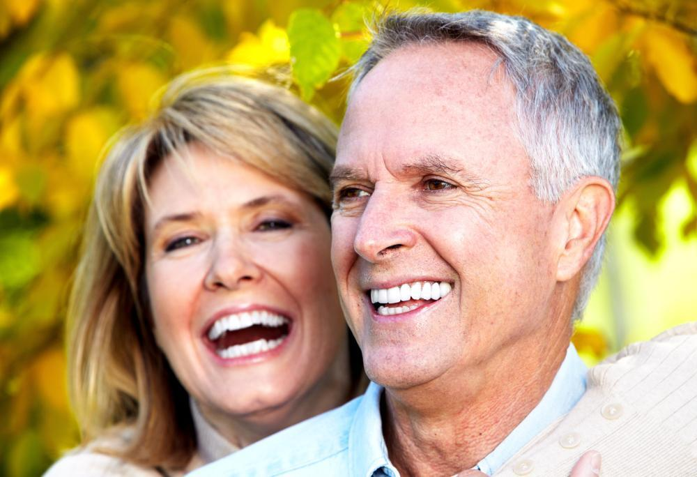 older man and woman smiling with yellow leaves in background