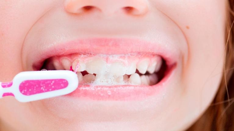 close up of child brushing teeth