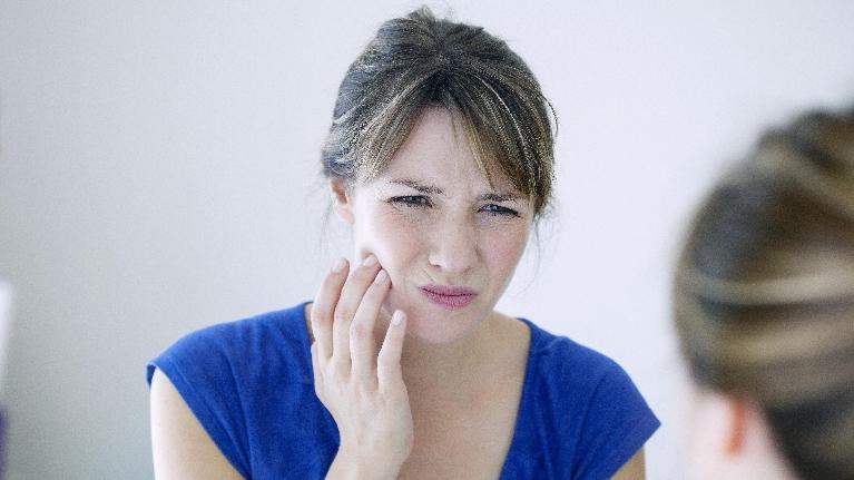 woman holding jaw during tooth emergency