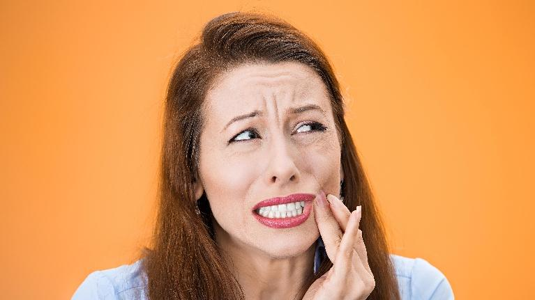 woman holding jaw while suffering from toothache