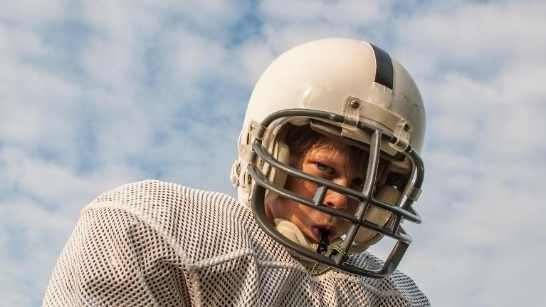 kid wearing football helmet with custom mouthguard